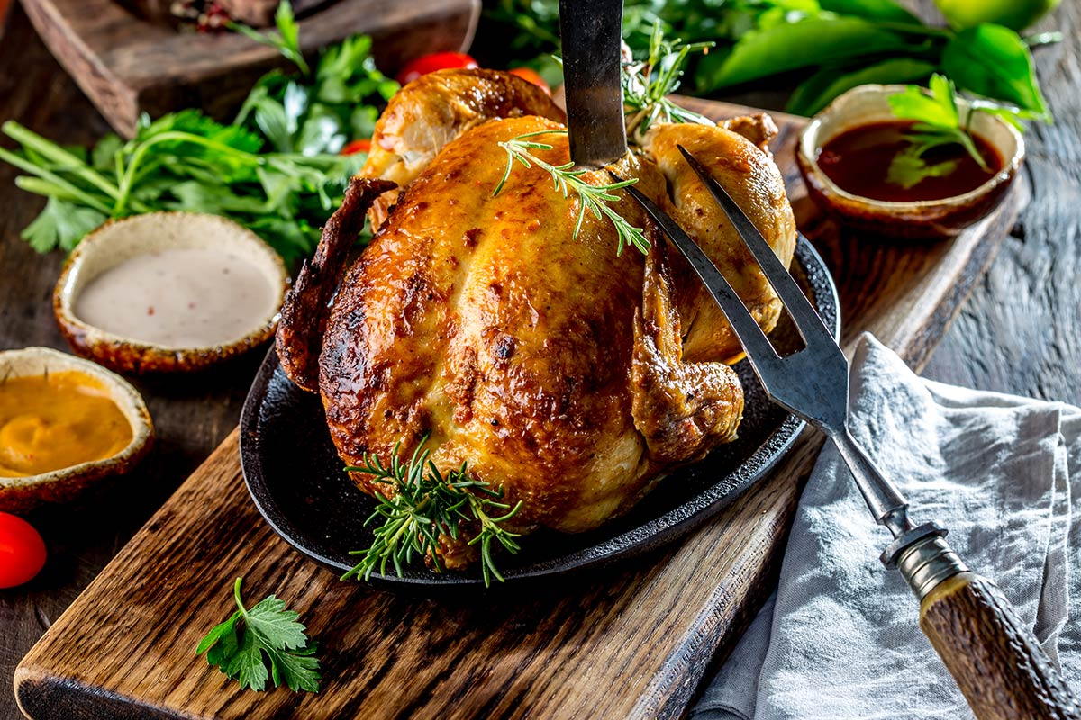 roasted-chicken-with-rosemary-and-sauces-on-wooden-KUGL84J
